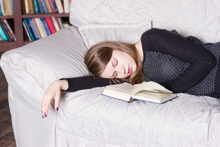 deprivation: Cute girl sleeping while holding a book lying on her bed Stock Photo