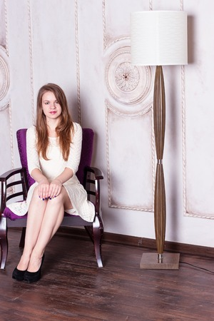 floor lamp: Attractive young woman sitting  in a chair next to a floor lamp. Vertical shot. Stock Photo