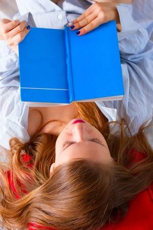 The girl in a mans shirt is reading a book in bed