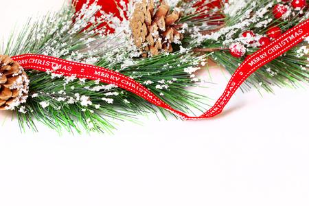 Kieferzweige mit Weihnachtsschmuck auf weiß