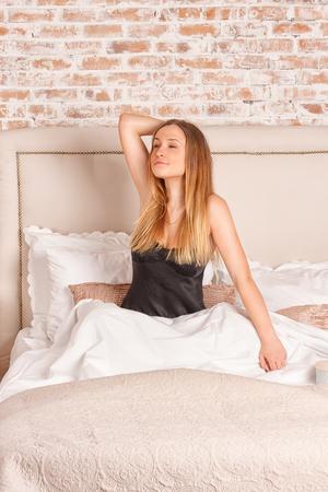 levantandose: Mujer que brilla intensamente que estira mientras que por la mañana