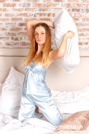 throw cushion: young teenage-woman is making a pillow-fight Stock Photo