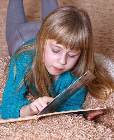 6 years girl: Girl 6 years old reading a book while lying on a carpet Stock Photo