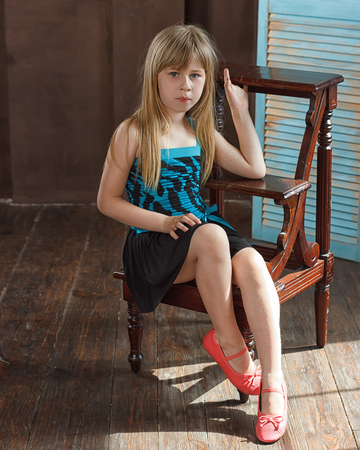 Girl 6 years old in dress sits on a chair near the blue wall photo