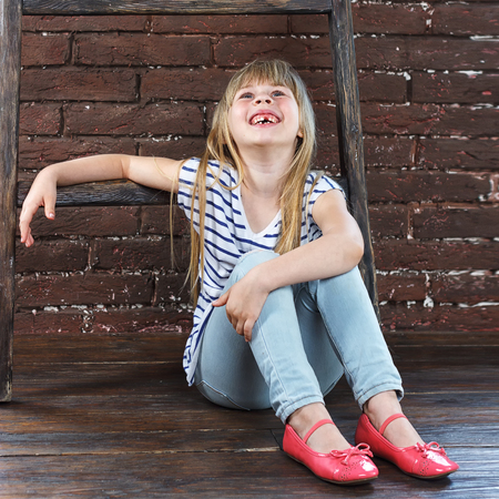 Girl 6 years old in jeans and a vest sits on the floor next to a brick wall and filled with laughter photo