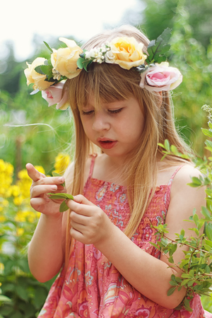 Cute little girl  on the meadow in summer day photo