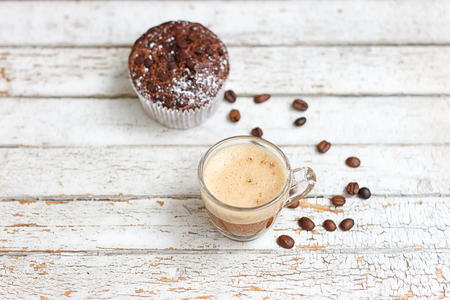 chocolate muffin and cup of coffee on the white wooden background