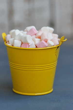 Yellow bucket full of marshmallow passage on the Board against white boards Stock Photo