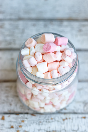 One glass jar filled up with marshmallow on white wooden background