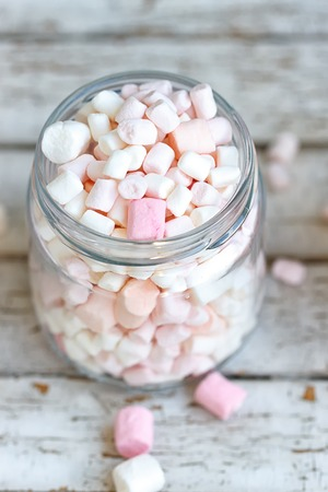 marshmellow: One glass jar filled up with marshmallow on white wooden background
