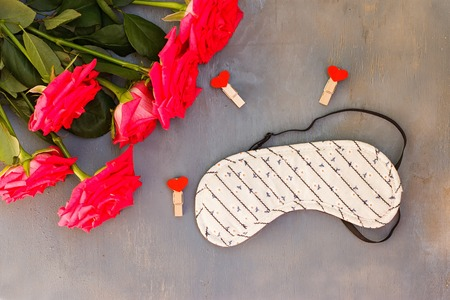 sleeping mask: sleeping mask and flowers on a blue background. Stock Photo