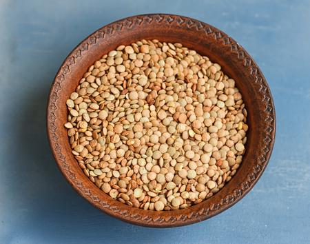 green lentil: Green lentil in wooden bowl, on blue background Stock Photo
