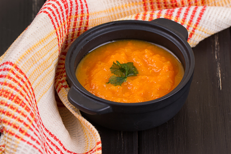 Pumpkin soup and small pumpkins on a wooden table.