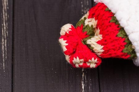 tejido de lana: gorro de lana de invierno con hilo rojo, blanco, verde Foto de archivo