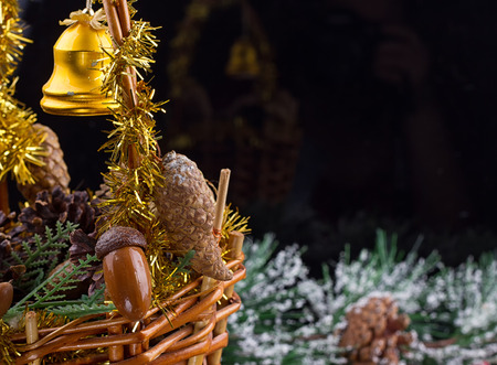 Christmas ornaments with garland of beads, pine cones and acorns laying in a basket with greens Stock Photo