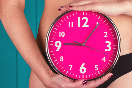 Biological clock ticking. Pink clock in female hands. toning