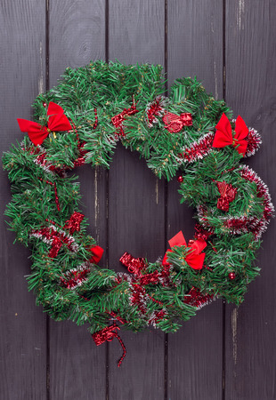Christmas wreath on a rustic wooden black front door.