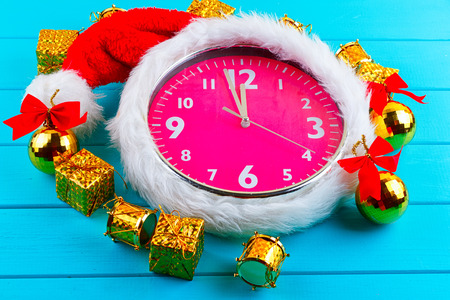 Fir tree with christmas decorations, alarm clock and gift boxes on blue background Stock Photo