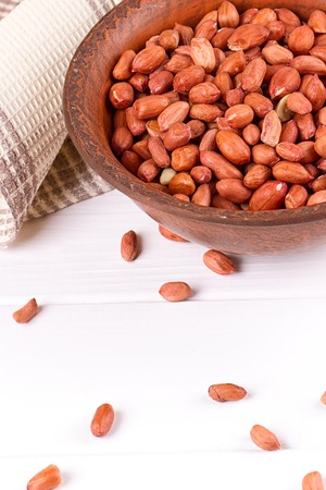 Peanuts in a brown plate. on white background Stock Photo