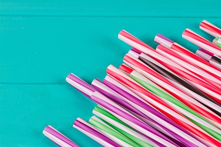Drinking straws for party on blue pastel background with copy space. Top view