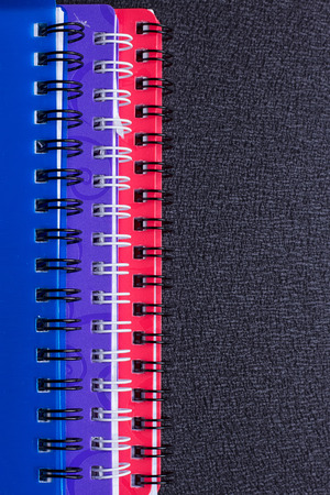 Several multi-colored notebooks on a spiral on a black background