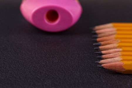 sharpened: Simple pencils and a pink pencil sharpener on a black background Stock Photo