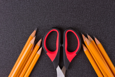 yellow notepad: Simple pencils and scissors on a black background Stock Photo