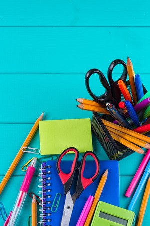 school and office supplies. school background. colored pencils, pen, pains, paper for school and student education on blue wood background. top view