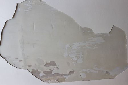 A big hole in the plastered white ceiling