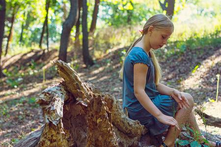 Girl sitting on a tree stump photo