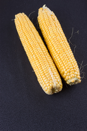 maize flour: Raw corn on the black wooden board Stock Photo