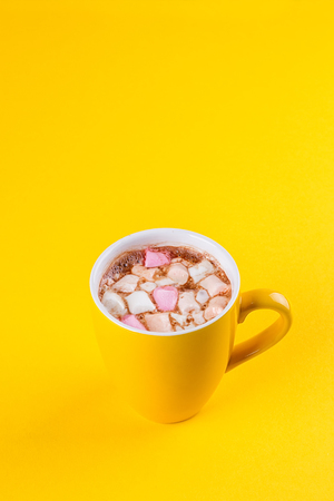 Yellow cup of hot cocoa with marshmallows on yellow background