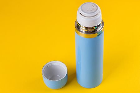 Blue thermos for hot drinks on a yellow background Stock Photo