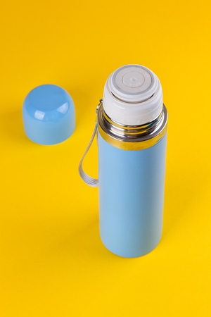 cup four: Blue thermos for hot drinks on a yellow background Stock Photo