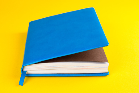 Blue closed diary on a yellow background Stock Photo