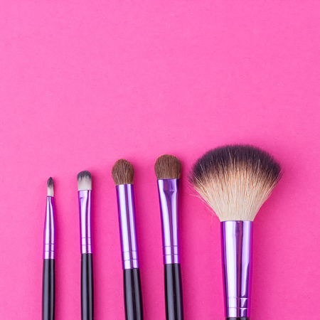 Set of makeup brushes on pink background. Top view point, flat lay.