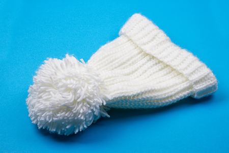 pom: White winter knitted cap on blue background