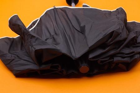 closed black umbrella on the orange background Stock Photo