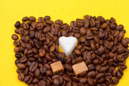 Coffee beans and sugar in the form of heart on a yellow background Stock Photo