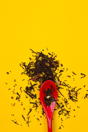 loose leaf: Tea composition with spoon on yellow background