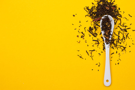 Tea composition with spoon on yellow background
