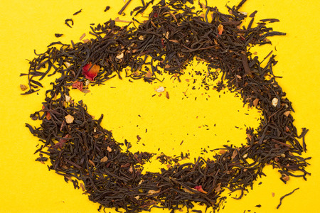 Aromatic tea with fruit, petals on the yellow background Stock Photo