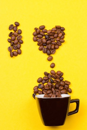 A cup of coffee and heart of the beans on yellow background