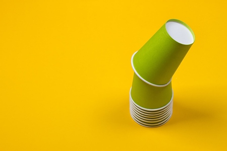 Set of green paper cups on a yellow background