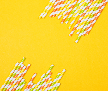 Colorful drinking straws on the yellow background Stock Photo