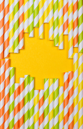 close-up colorful fancy drinking straws, fancy tube for party on the yellow background