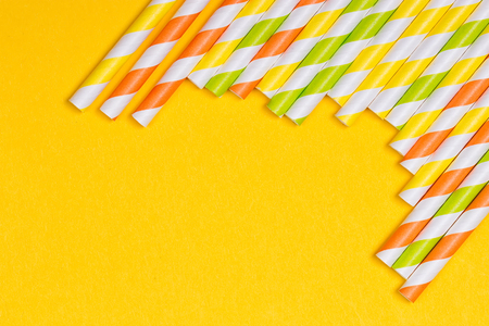 artsy: close-up colorful fancy drinking straws, fancy tube for party on the yellow background