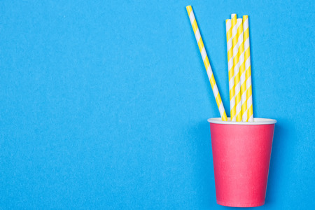 a bundle of multi-colored drinking straws in a paper Cup on a blue background. fashion minimal. flat lay