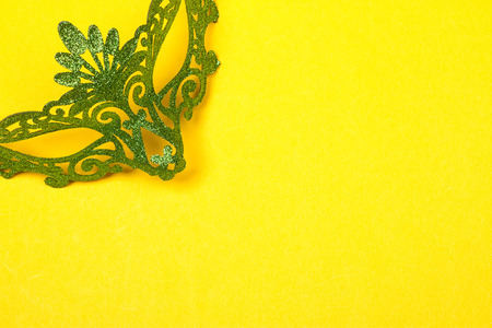 Green, mardi gras mask on a bright yellow background