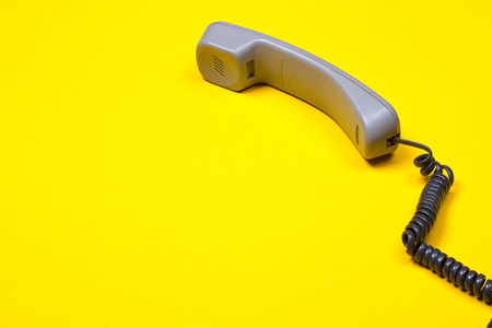 Top view of gray telephone handset. receiver and cord on yellow background.